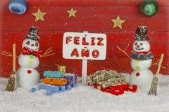 Dos muñecos de nieve con una Feliz Año Nuevo señalizan con las palabras escritas en español Fotografía de archivo