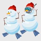 Dos muñecos de nieve en casquillo rojo y con el buceador de las aletas Fotos de archivo libres de regalías