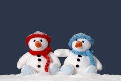 Dos muñecos de nieve lindos que se sientan en la nieve Imagenes de archivo