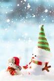 Dos muñecos de nieve que se colocan en la nieve Imágenes de archivo libres de regalías