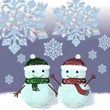 Dos muñecos de nieve se están colocando debajo de los copos de nieve Fotos de archivo