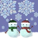Dos muñecos de nieve se están colocando debajo de los copos de nieve Fotografía de archivo libre de regalías