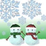 Dos muñecos de nieve se están colocando debajo de los copos de nieve Fotos de archivo libres de regalías