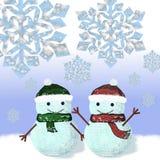 Dos muñecos de nieve vestidos en casquillos y bufandas hechos punto Imagenes de archivo