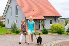 Dos muchacha o niños que recorren con el perro Imágenes de archivo libres de regalías