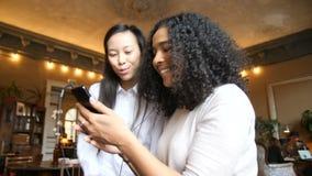Dos muchachas étnicas multi gozan el usar de tecnología elegante del teléfono para escuchar la música con los auriculares en el c almacen de video