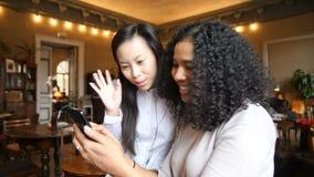 Dos muchachas étnicas multi que se divierten usando tecnología elegante del teléfono en café metrajes