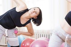 Dos muchachas activas de la aptitud que ejercitan con los Barbells dentro en gimnasio Imágenes de archivo libres de regalías