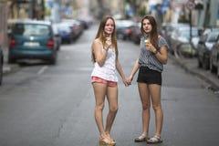 Dos muchachas adolescentes con helado se colocan en la calle que lleva a cabo las manos El caminar Imagen de archivo libre de regalías