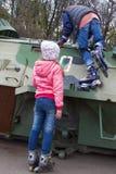 Dos muchachas adolescentes con los rodillos en el vehículo de lucha de Bradley de la guerra Imagen de archivo libre de regalías