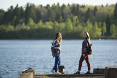 Dos muchachas adolescentes de los amigos pasan el tiempo junto en el embarcadero Fotos de archivo