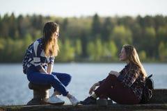 Dos muchachas adolescentes de los amigos pasan el tiempo junto en el embarcadero del río Naturaleza Imagenes de archivo