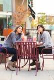 Dos muchachas adolescentes en el té de consumición del boba del café al aire libre junto Foto de archivo libre de regalías