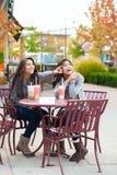 Dos muchachas adolescentes en el té de consumición del boba del café al aire libre junto Foto de archivo