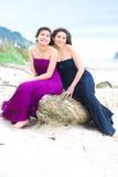 Dos muchachas adolescentes en vestidos elegantes que sonríen junto en la playa Imagen de archivo libre de regalías
