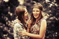 Dos muchachas adolescentes felices que caminan en bosque del verano Imagen de archivo libre de regalías