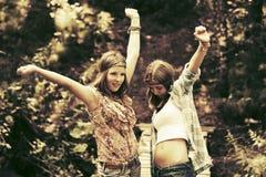 Dos muchachas adolescentes felices que caminan en bosque del verano Fotografía de archivo libre de regalías