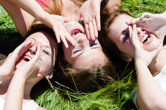 Dos muchachas adolescentes felices que mienten en hierba verde Foto de archivo libre de regalías
