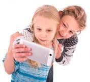 Dos muchachas adolescentes hacen el selfie en un fondo blanco Imagen de archivo