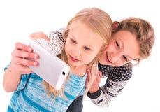 Dos muchachas adolescentes hacen el selfie en un fondo blanco Imágenes de archivo libres de regalías