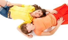 Dos muchachas adolescentes mienten de lado a lado Foto de archivo