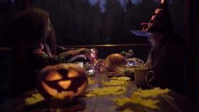 Dos muchachas adolescentes que comparten candys después de truco o de la invitación el la noche de Halloween almacen de video