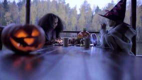 Dos muchachas adolescentes que comparten candys después de truco o de la invitación en Halloween metrajes