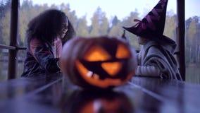 Dos muchachas adolescentes que comparten candys después de truco o de la invitación en Halloween almacen de metraje de vídeo
