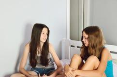 Dos muchachas adolescentes que hablan sentarse en la cama en el cuarto Foto de archivo