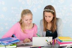 Dos muchachas adolescentes que hacen la preparación así como la tableta digital Imagenes de archivo