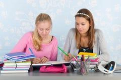 Dos muchachas adolescentes que hacen la preparación junta Fotos de archivo libres de regalías