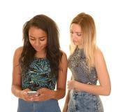 Dos muchachas adolescentes que mandan un SMS en el fondo blanco Fotos de archivo