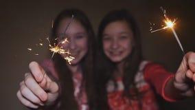 Dos muchachas adolescentes que presentan y bengalas encendidas sonrientes metrajes