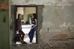 Dos muchachas adolescentes que se colocan en el pasillo en un edificio abandonado Amistad Imágenes de archivo libres de regalías