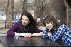 Dos muchachas adolescentes que se sientan en café de la calle Imagenes de archivo