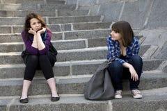 Dos muchachas adolescentes que se sientan en las escaleras Imagen de archivo libre de regalías