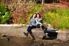 Dos muchachas adolescentes que se sientan en roca a lo largo del lago en otoño Foto de archivo libre de regalías
