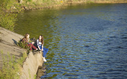 Dos muchachas adolescentes que se sientan en un embarcadero cerca del agua Naturaleza Imagen de archivo