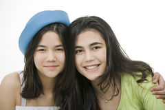 Dos muchachas adolescentes que sonríen junto, abrazando. Imagen de archivo libre de regalías
