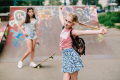 Dos muchachas adolescentes urbanas que presentan en parque del patín Fotografía de archivo
