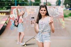 Dos muchachas adolescentes urbanas que presentan en parque del patín Foto de archivo