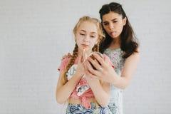 Dos muchachas adolescentes urbanas que presentan en un cuarto del vintage Fotos de archivo libres de regalías