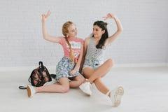 Dos muchachas adolescentes urbanas que presentan en un cuarto del vintage Imagen de archivo libre de regalías