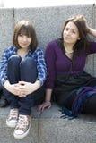 Dos muchachas adolescentes urbanas que se sientan en las escaleras Foto de archivo libre de regalías