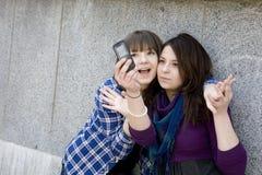 Dos muchachas adolescentes urbanas que toman la foto por el teléfono móvil Fotografía de archivo