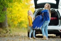 Dos muchachas adorables con una maleta que va el vacaciones con sus padres Dos niños que miran adelante para un viaje por carrete Imagenes de archivo