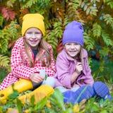 Dos muchachas adorables en bosque en el otoño soleado caliente Foto de archivo