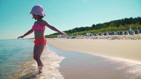Dos muchachas adorables en trajes de baño están jugando en el mar almacen de video