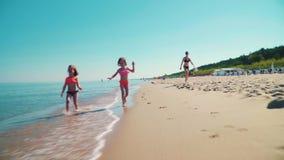 Dos muchachas adorables están corriendo en una playa arenosa por el mar almacen de metraje de vídeo
