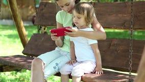 Dos muchachas agradables con smartphone rojo se sientan en el banco del oscilación en jardín almacen de metraje de vídeo